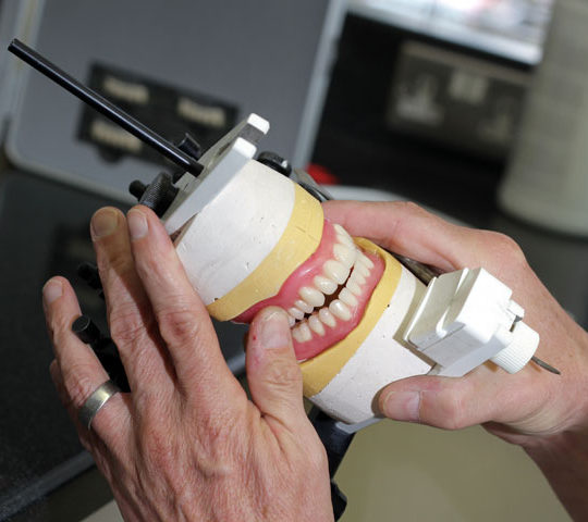 a pair of dentures being checked in a specialist tool